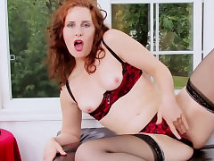 Ginger-haired chick moans while she masturbates