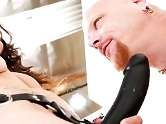 She is dressed in a giant ebony strap-on and is measuring it to his dick